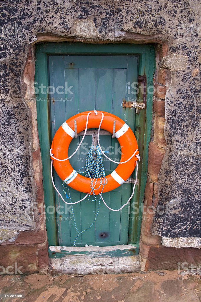life saving buoy on old wooden door royalty-free stock photo