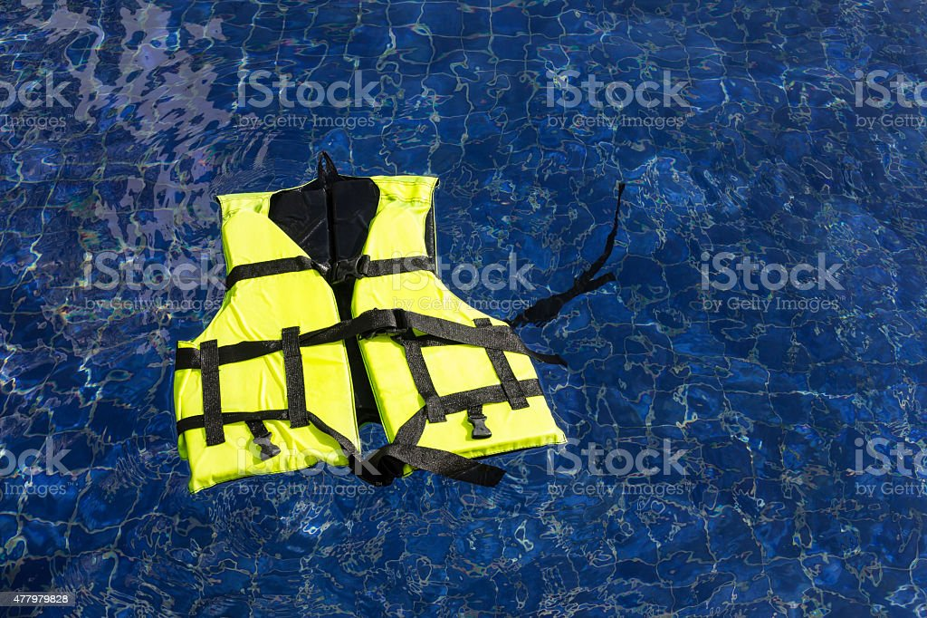 Life vest floating in swimming pool stock photo