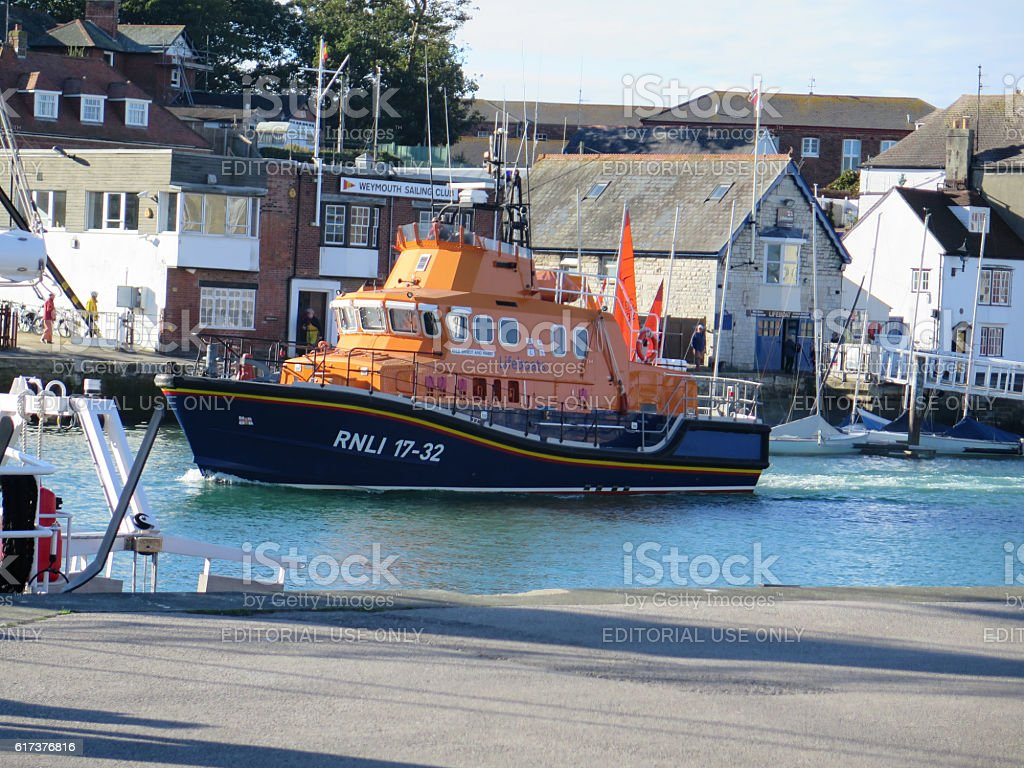 RNLI lifeboat entering Weymouth harbor in Dorset, UK stock photo