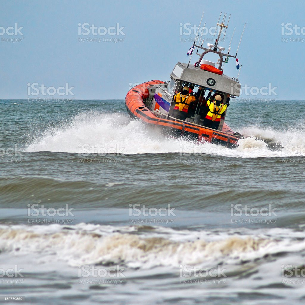 A lifeboat rides a wave as it sets off into action stock photo