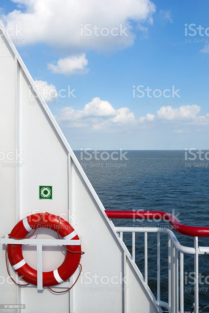 lifebuoy and part of ship at sea with blue sky stock photo