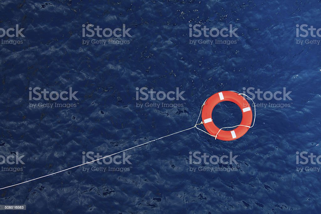 Lifebuoy in a stormy blue sea, safety equipment in boat stock photo