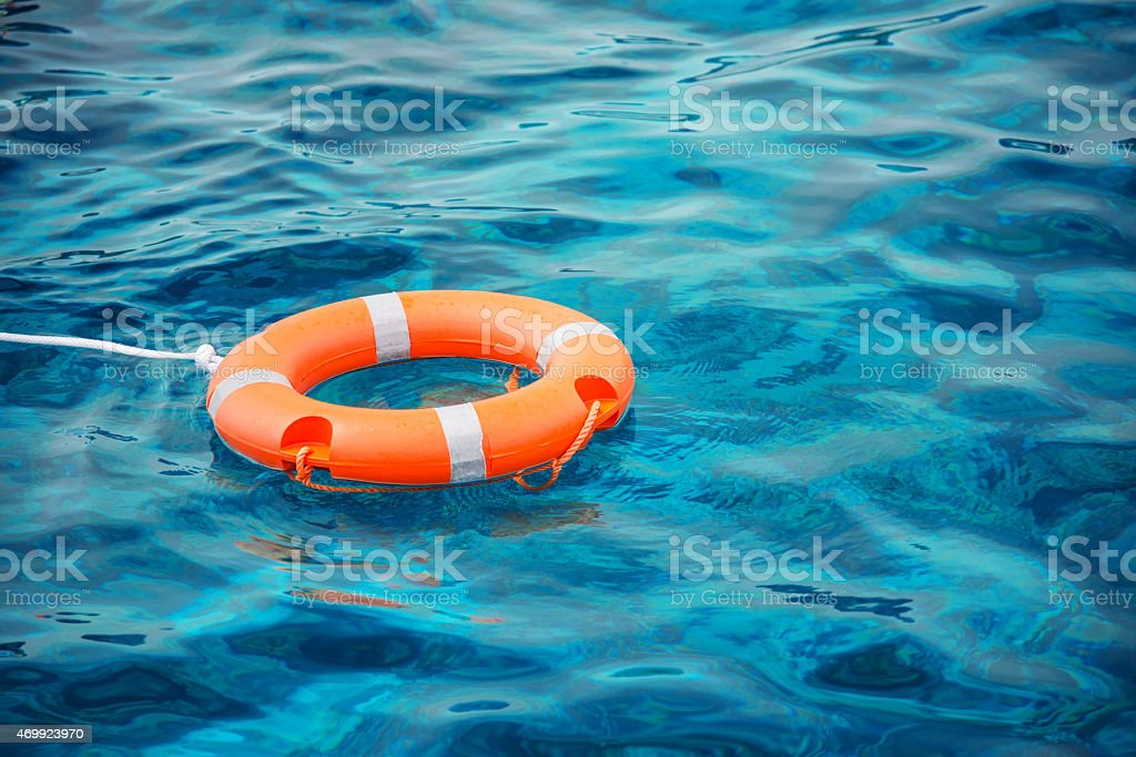 Lifebuoy resting on top of blue waters stock photo
