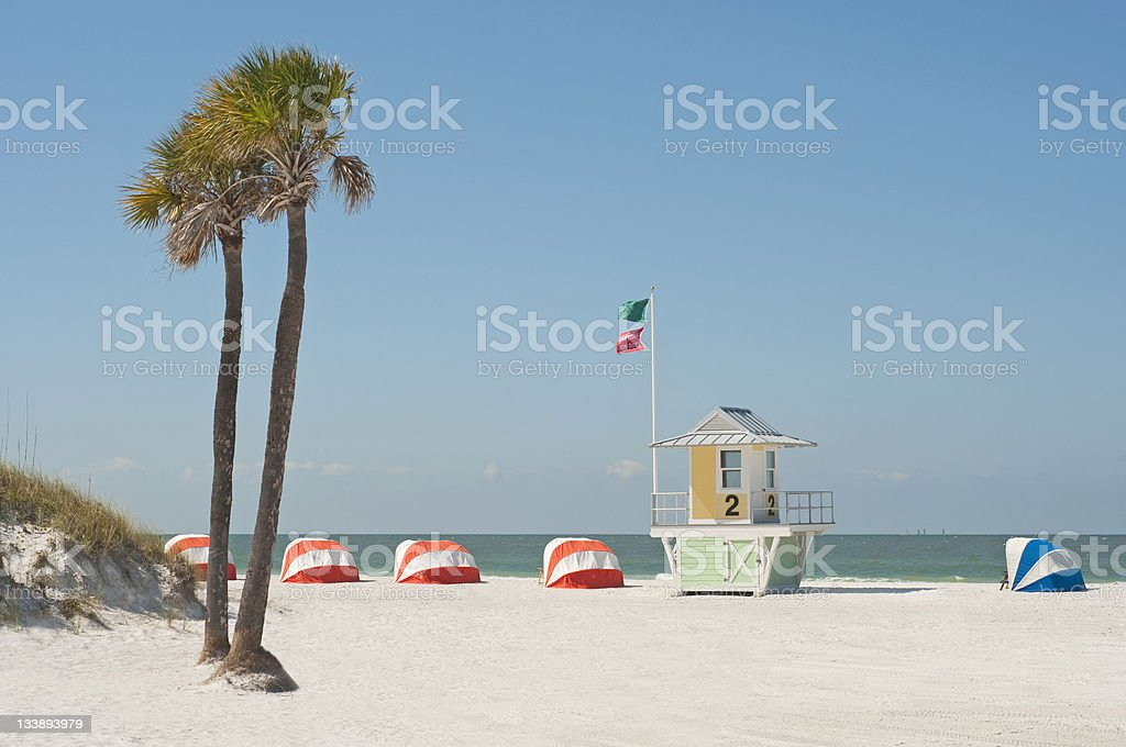 Lifeguard hut on beach with palm trees and beach tents stock photo