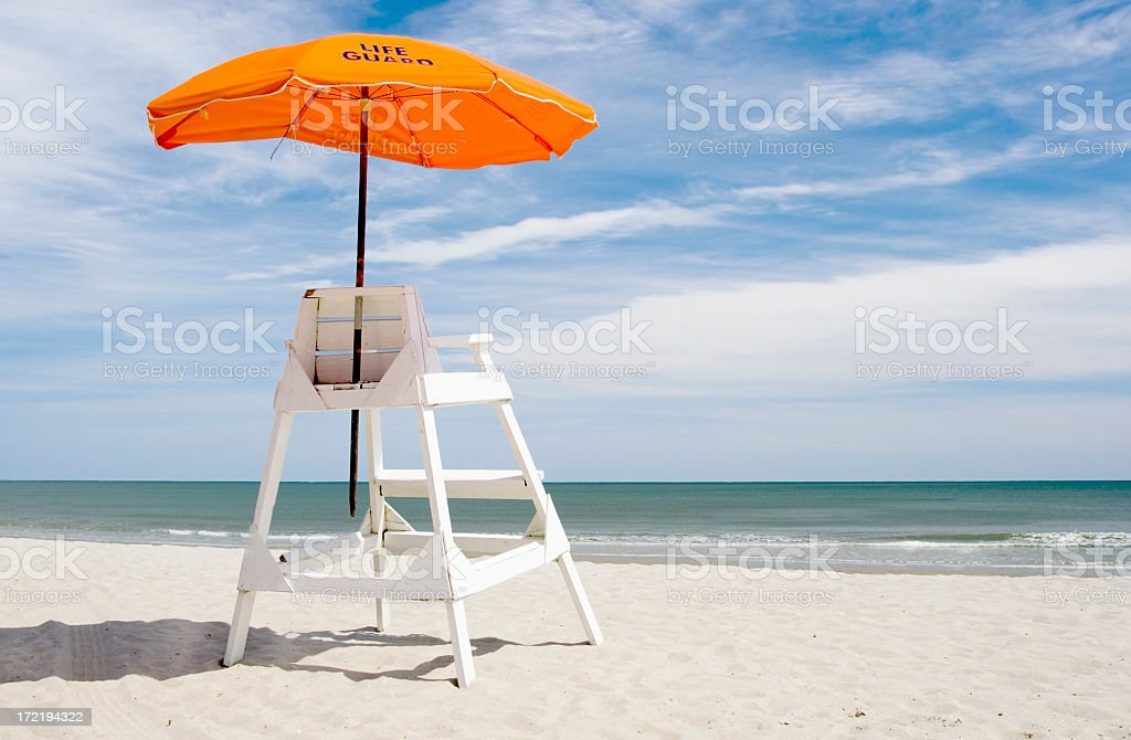 A lifeguard station on the beach with an orange umbrella stock photo