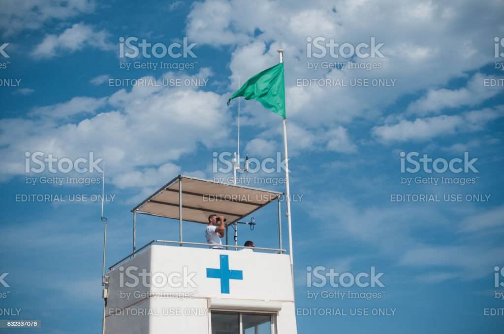 lifeguard station with green flag stock photo