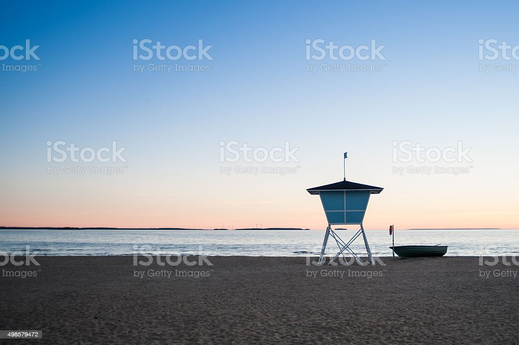 Lifeguard tower and a boat on the beach at sunset stock photo