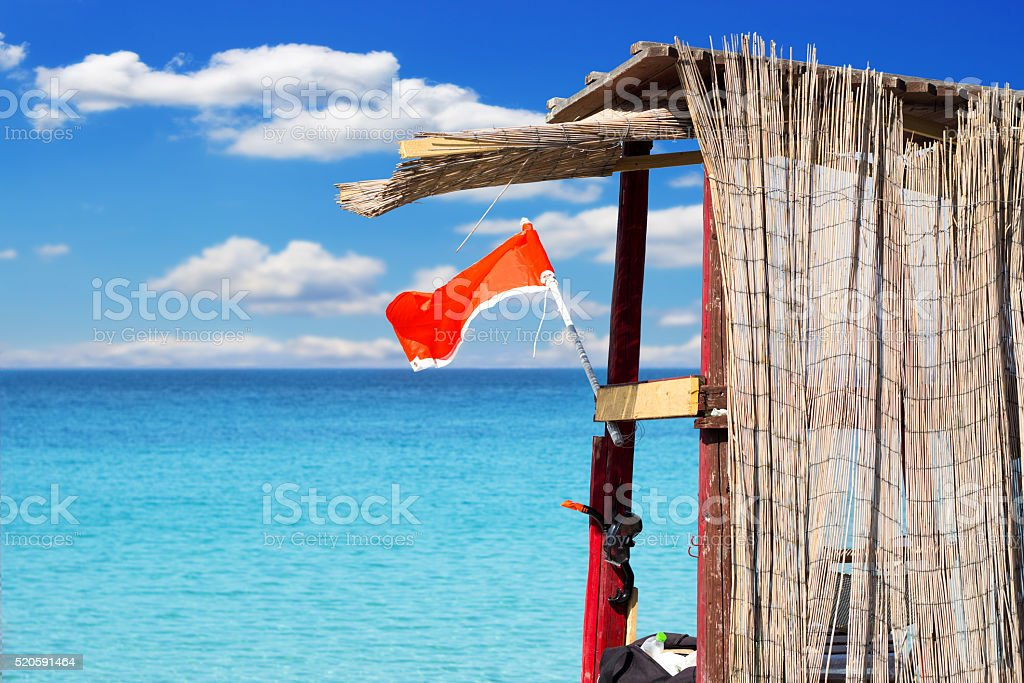Lifeguard tower on the beach with red flag stock photo