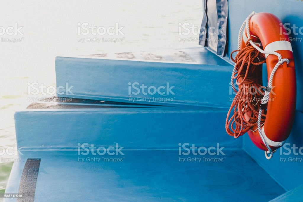 lifesaver on a blue boat moored to the sea stock photo