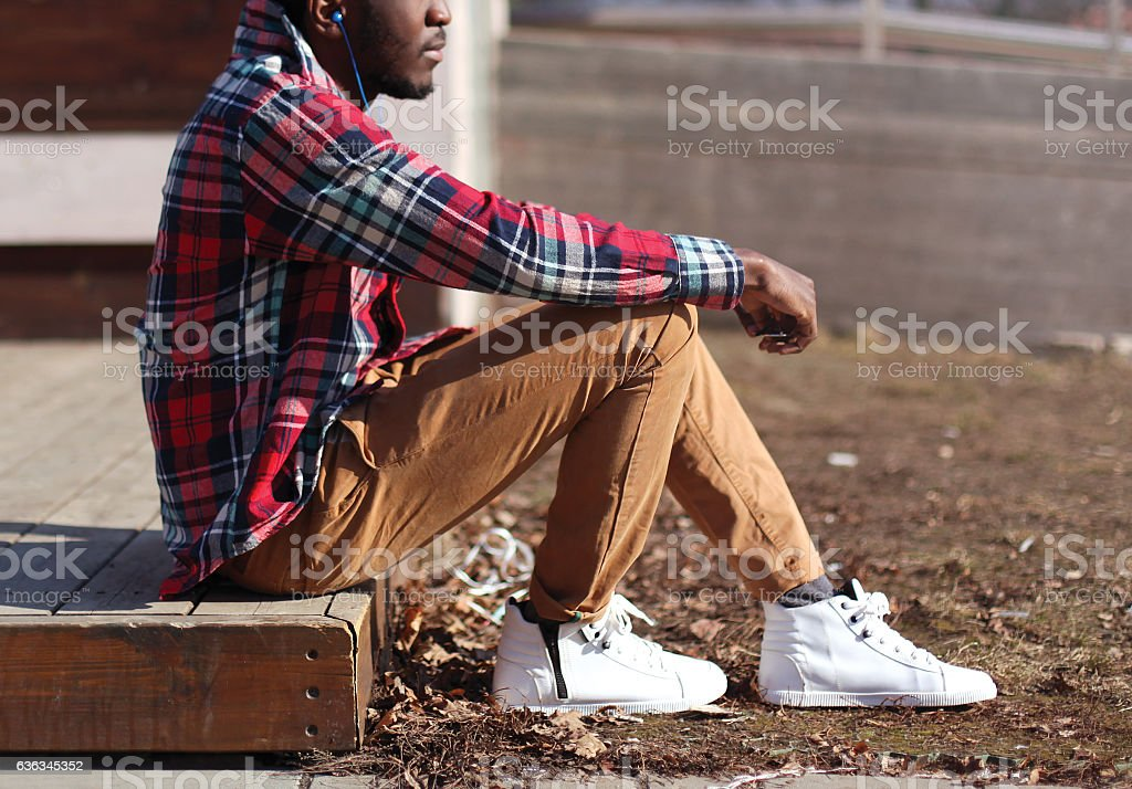Lifestyle fashion photo stylish african man listens music stock photo