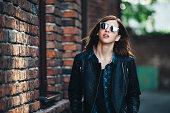 Lifestyle fashion portrait of brunette girl in rock black style