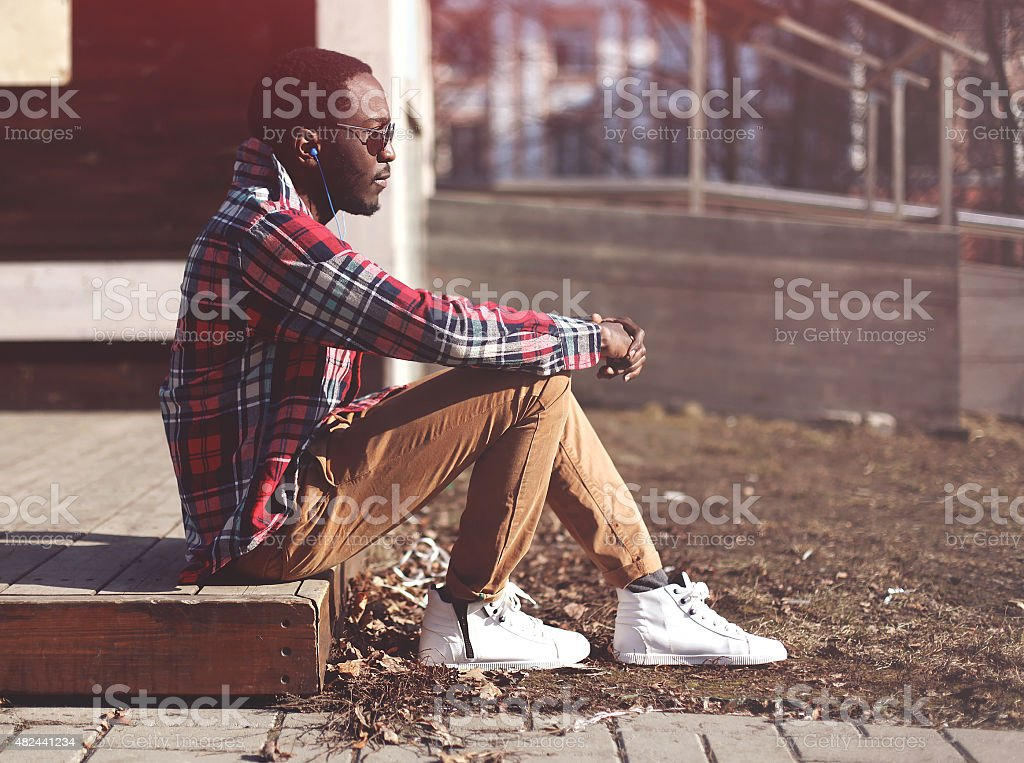 Lifestyle fashion portrait of stylish young african man listens stock photo