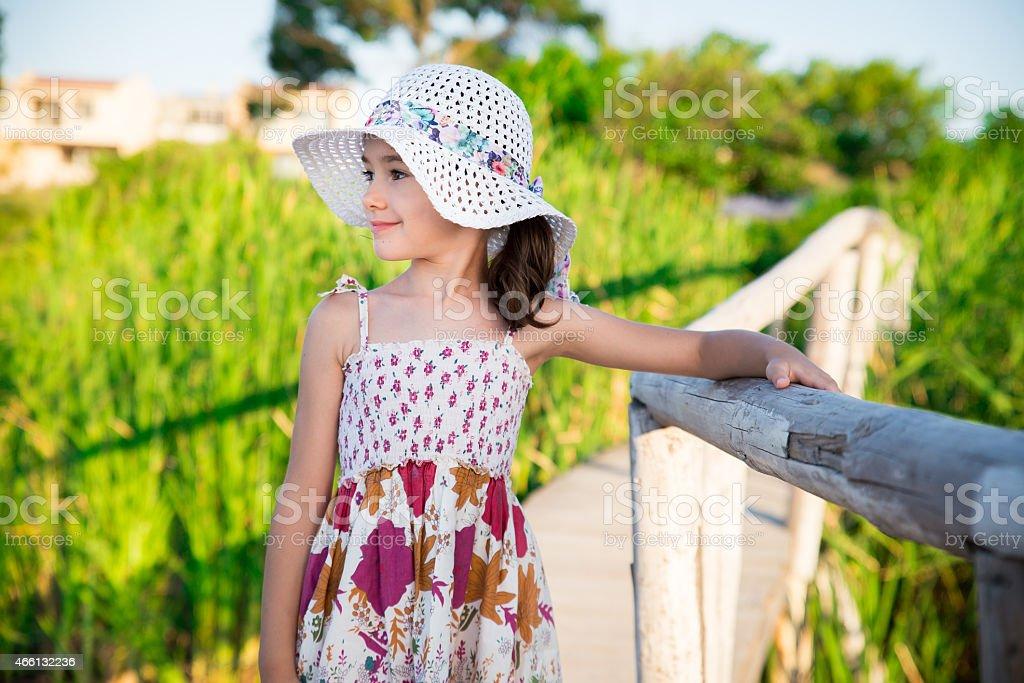 Lifestyle portrait of happy white Caucasian girl wearing floppy hat stock photo