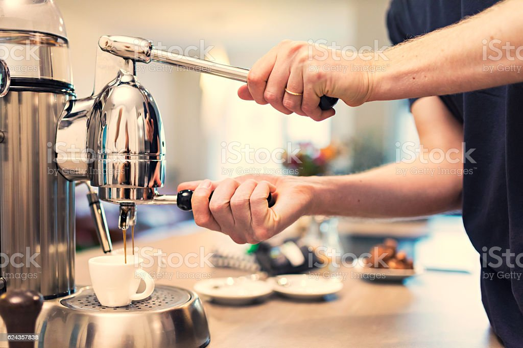 Lifestyle - Young man making espresso at home stock photo