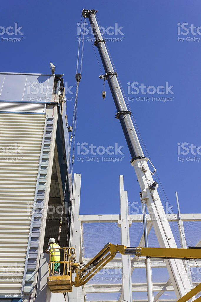 Lift for workers on metal girders at a new construction royalty-free stock photo