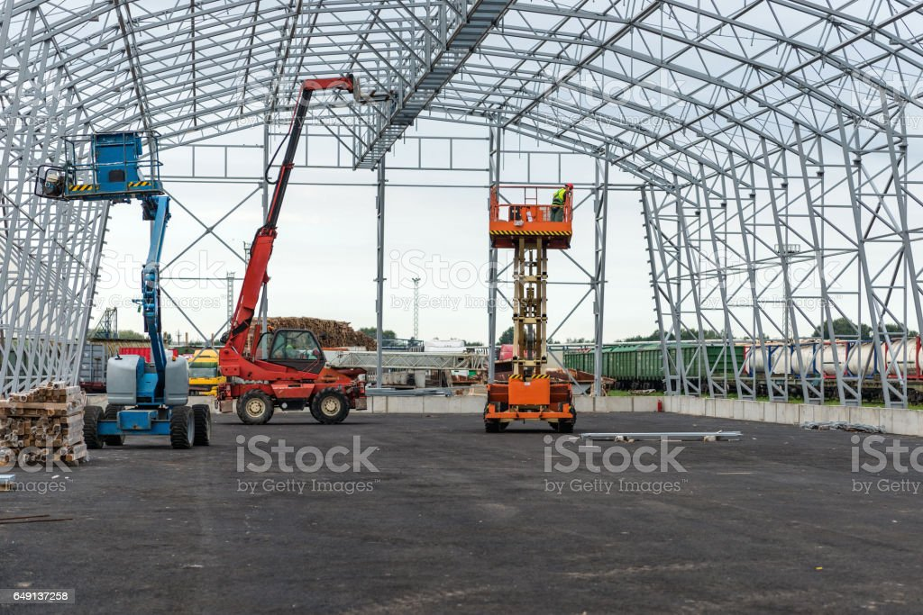 Lift with platform work in warehouse hangar construction field. stock photo