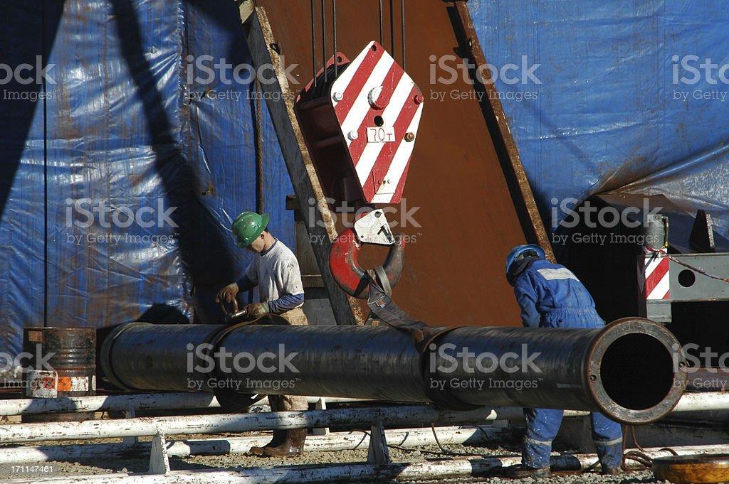 Lifting heavy pipe royalty-free stock photo