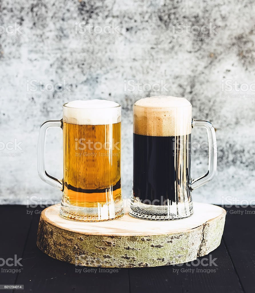 Light and dark beer in mugs on wooden board, grunge stock photo