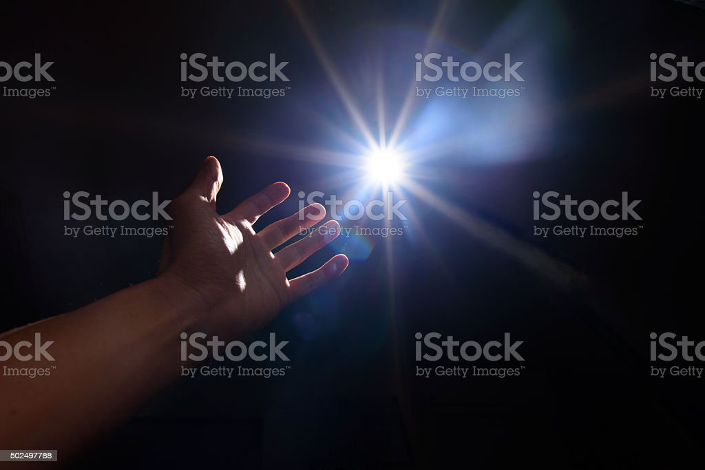 light and hand in the dark stock photo