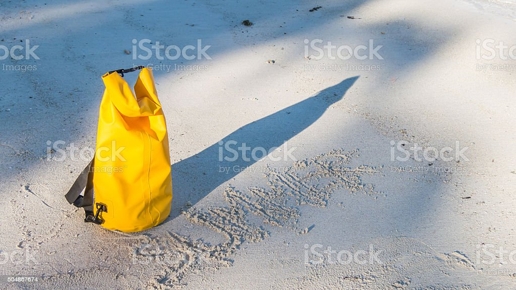 Light and shadow on sandy beach with yellow waterproof bag stock photo