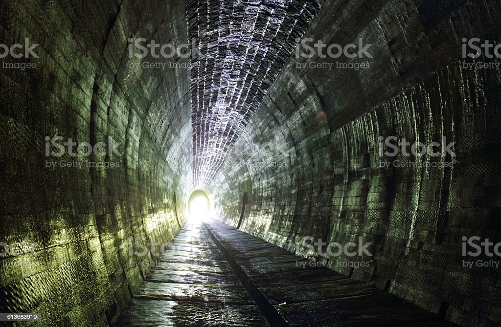 Light at the and of tunnel.Ancient cemetery around stock photo