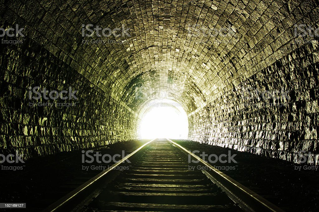 Light at the end of a brick tunnel with train tracks stock photo