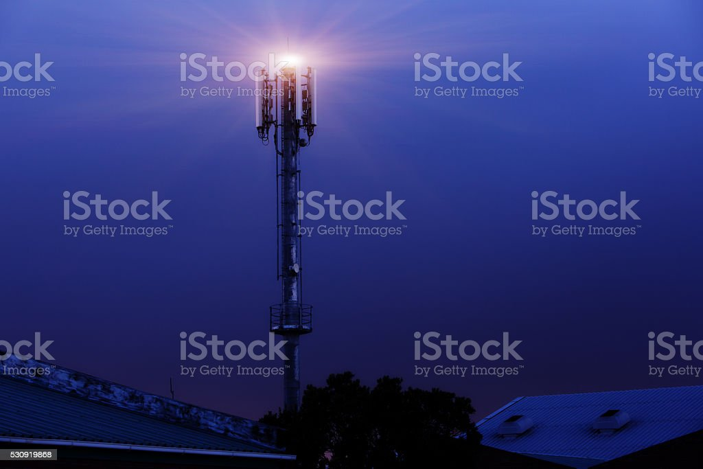 Light atop cellphone tower at night stock photo