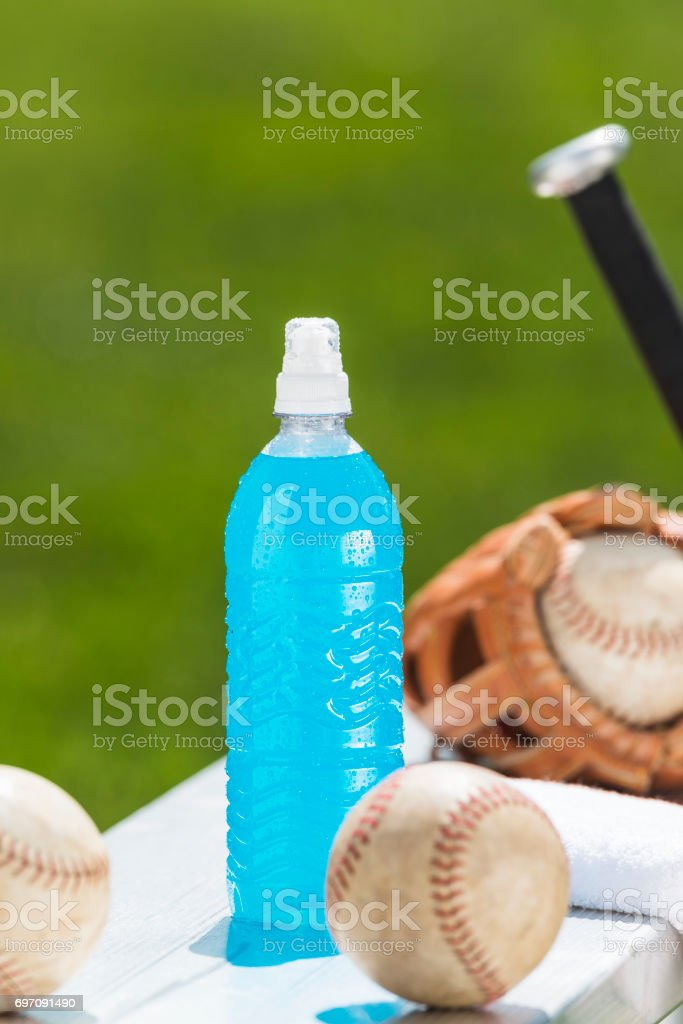 Light blue sports drink on bench with softball equipment stock photo