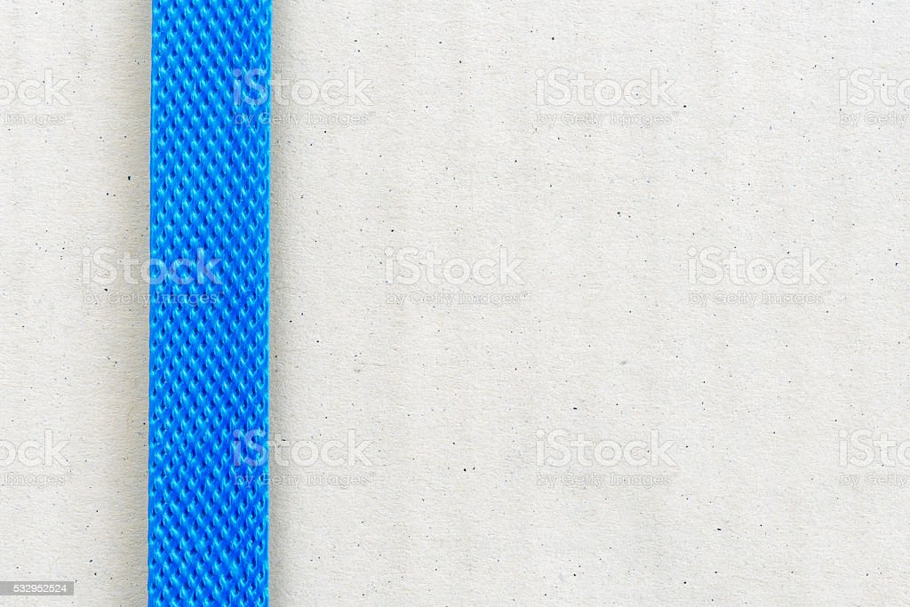 Light brown cardboard box fastened with blue plastic strap. stock photo