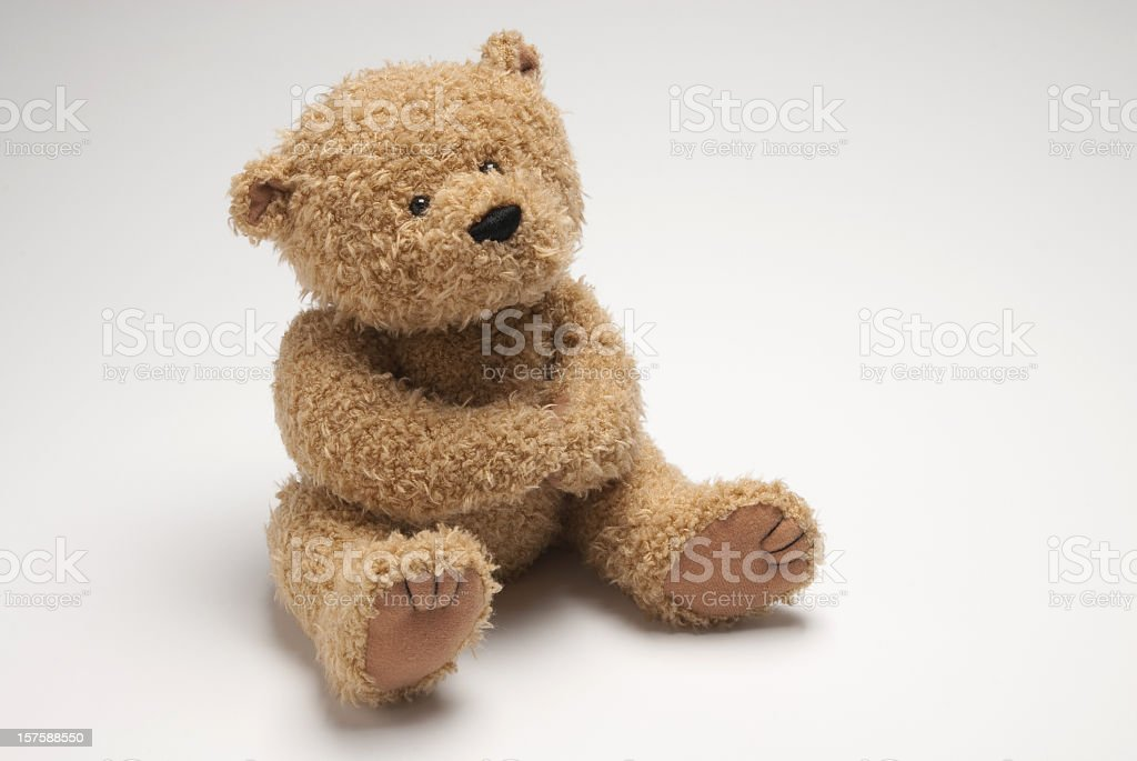 Light brown stuffed bear sitting on white surface stock photo