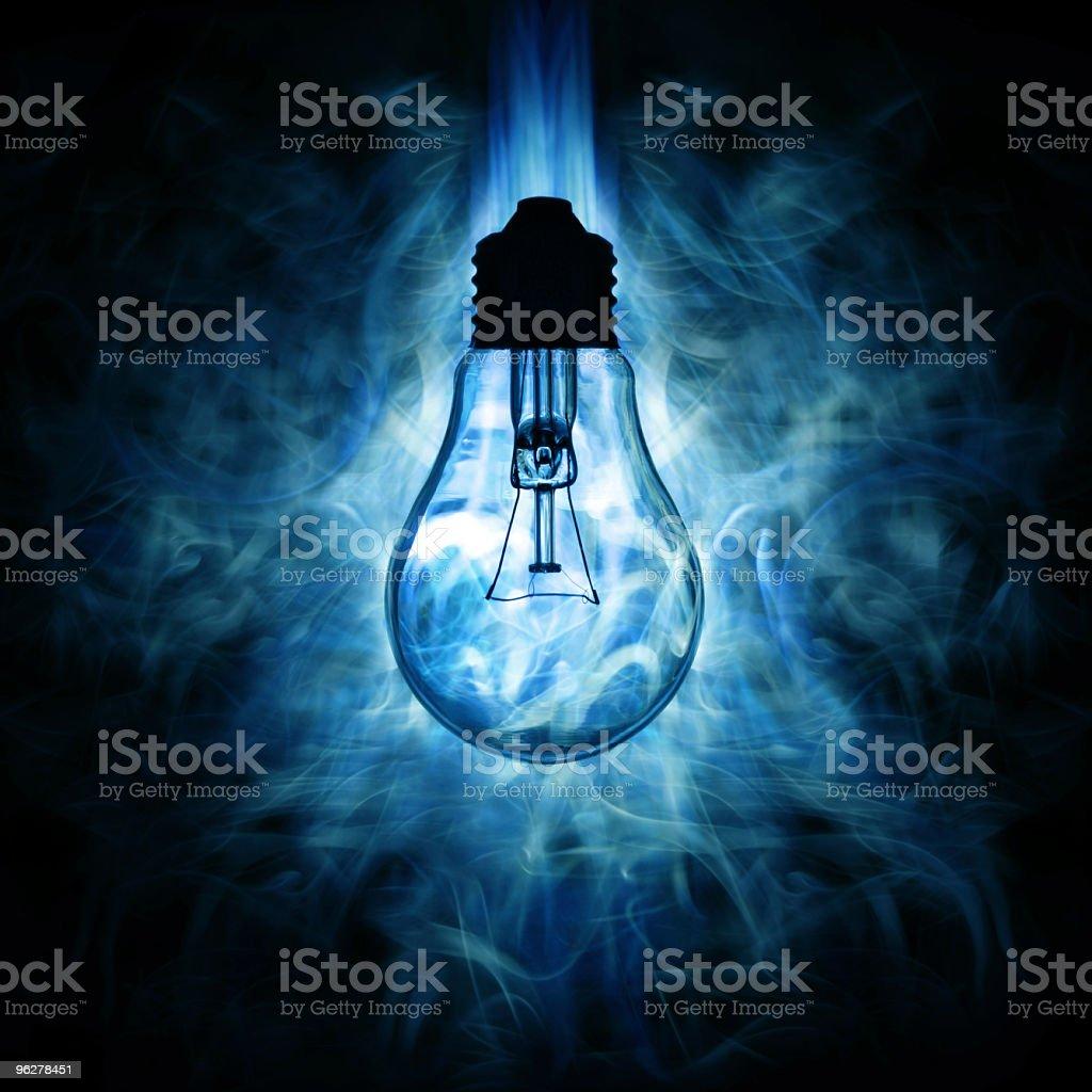 Light bulb and blue smoky light background royalty-free stock photo