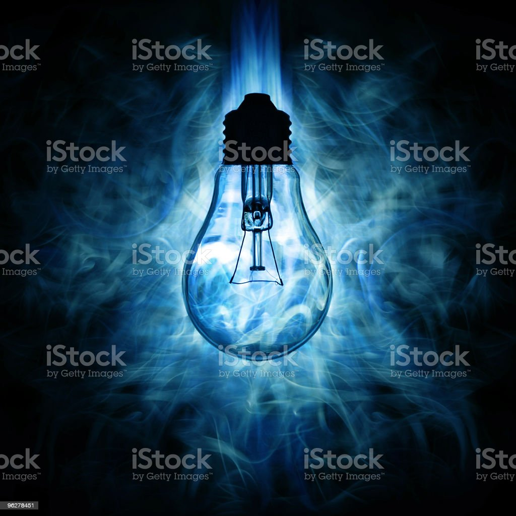 Light bulb and blue smoky light background stock photo