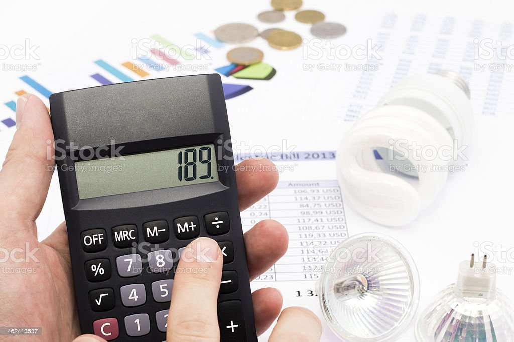 Light bulb, calculator and euro coins stock photo