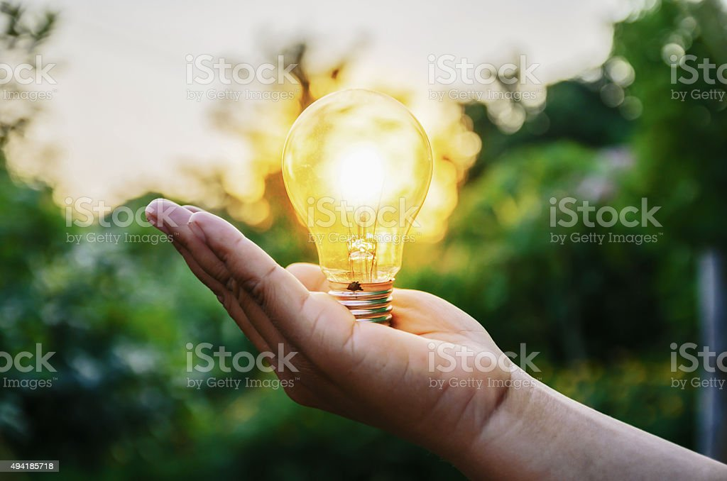 light bulb from sunset on hand concept stock photo