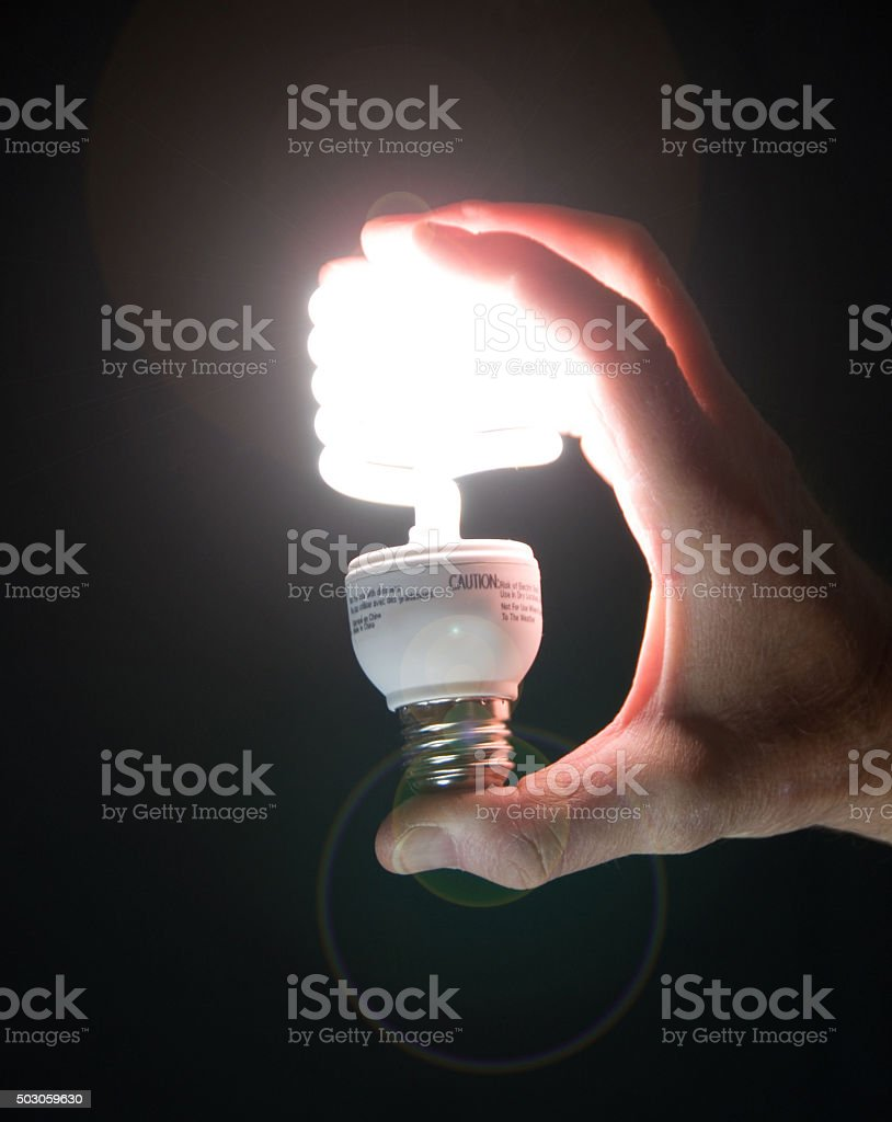 CFL Light Bulb ... Hand held on Black with Flare stock photo