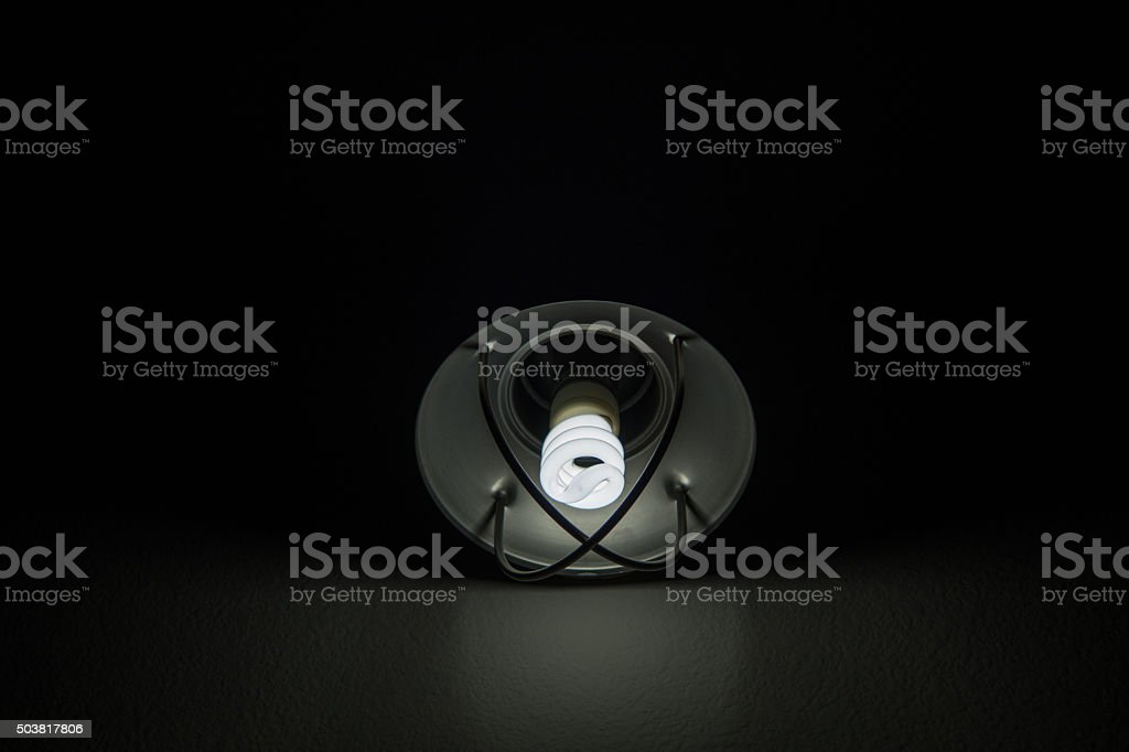 light bulb in dark hallway - industrial stock photo