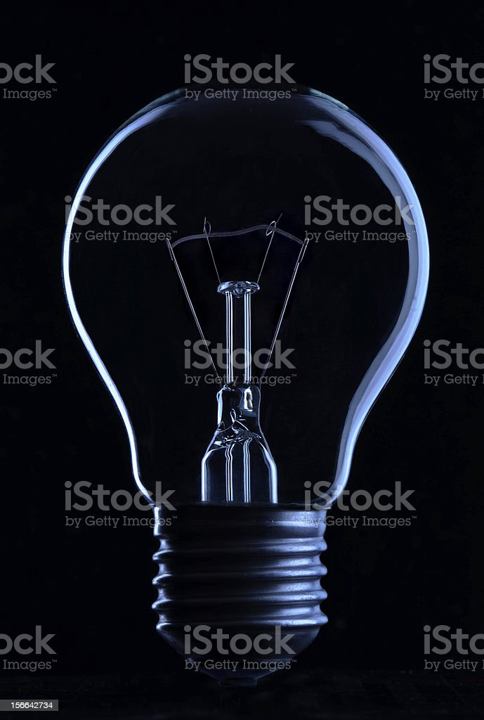 Light bulb in the dark with blue hues stock photo