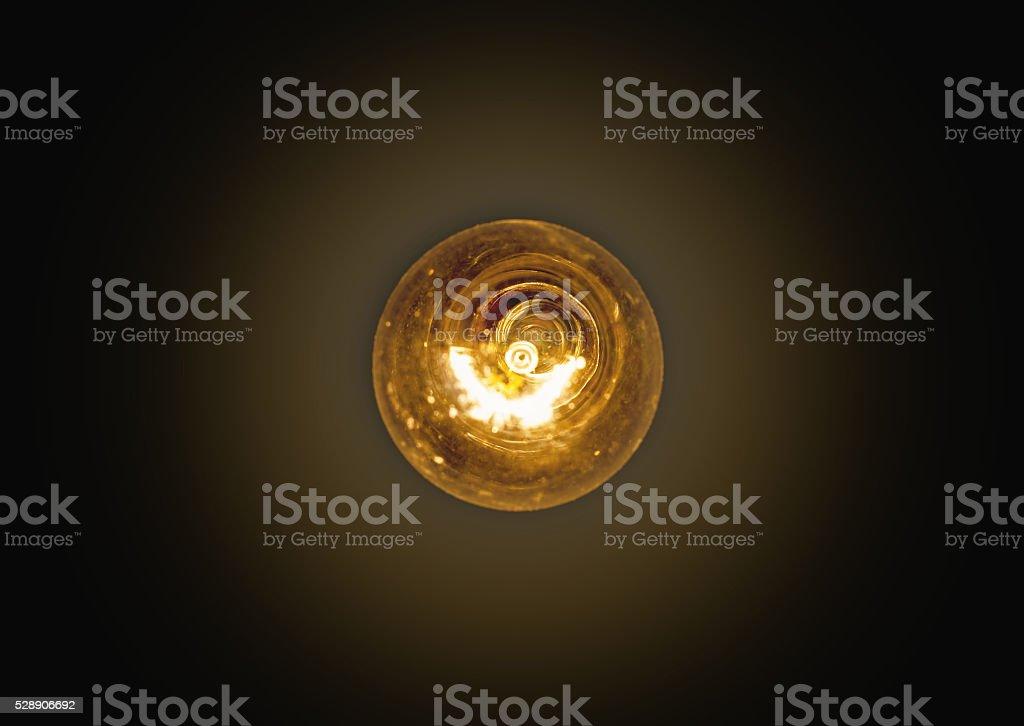 light bulb lit on a black background stock photo