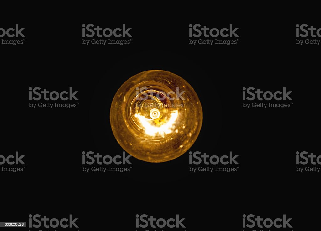 light bulb lit on a black background stock photo