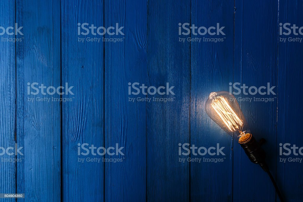 Light bulb on blue wood stock photo