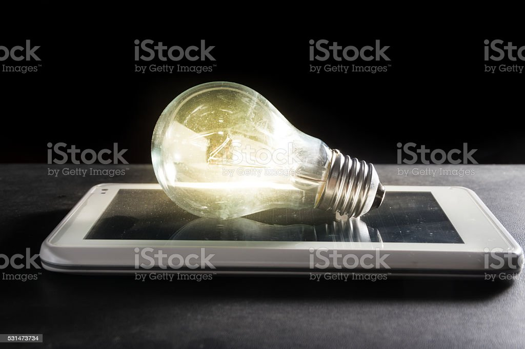 Light bulb on computer tablet. stock photo