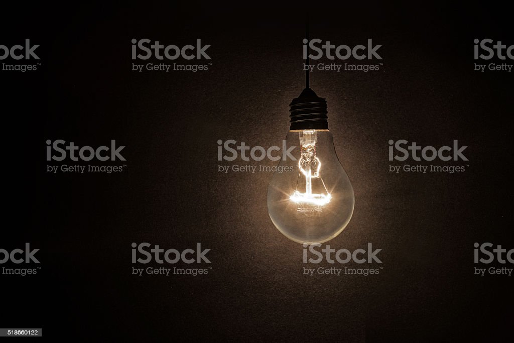 light bulb on dark background stock photo