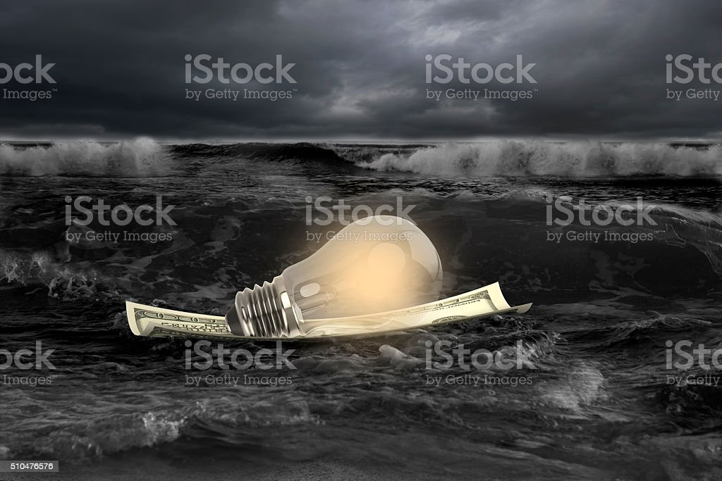Light bulb on money boat in stormy sea stock photo
