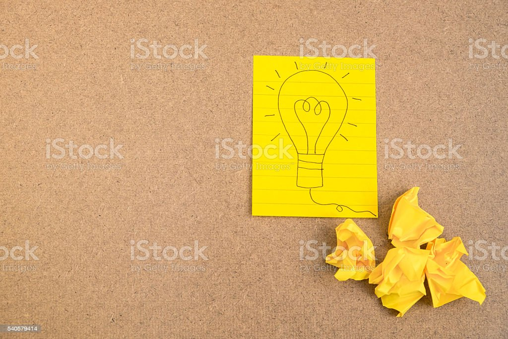 Light bulb on yellow paper with crumpled paper stock photo