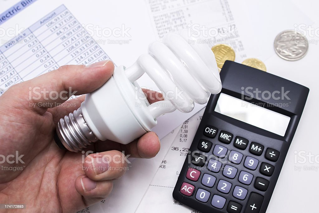 Light bulb whit calculator and coins stock photo