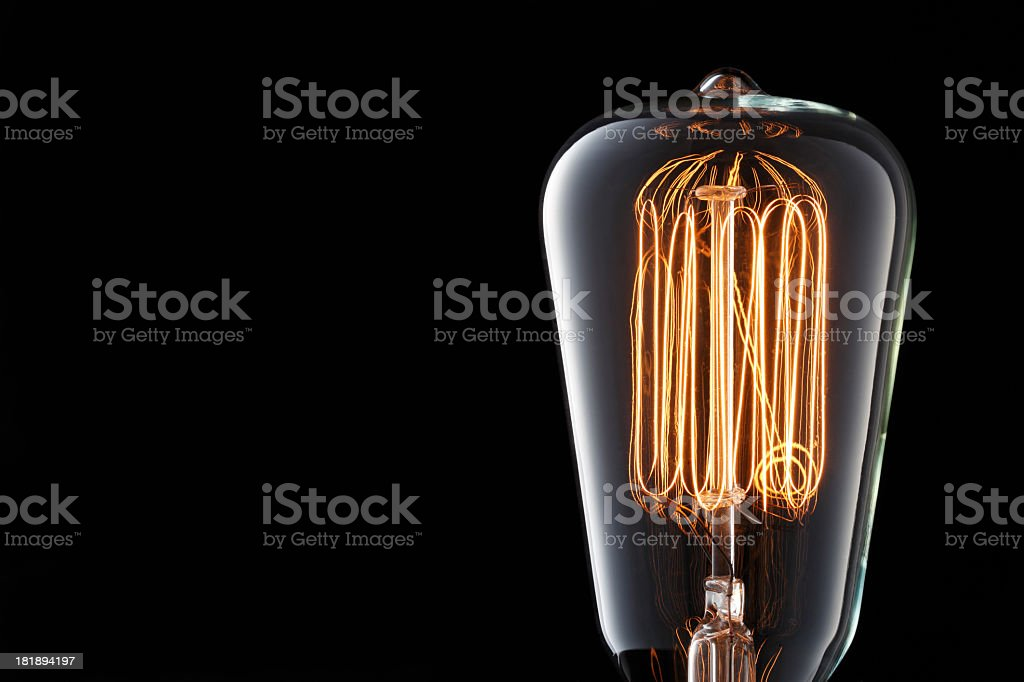 Light bulb with multiple filaments on black background stock photo