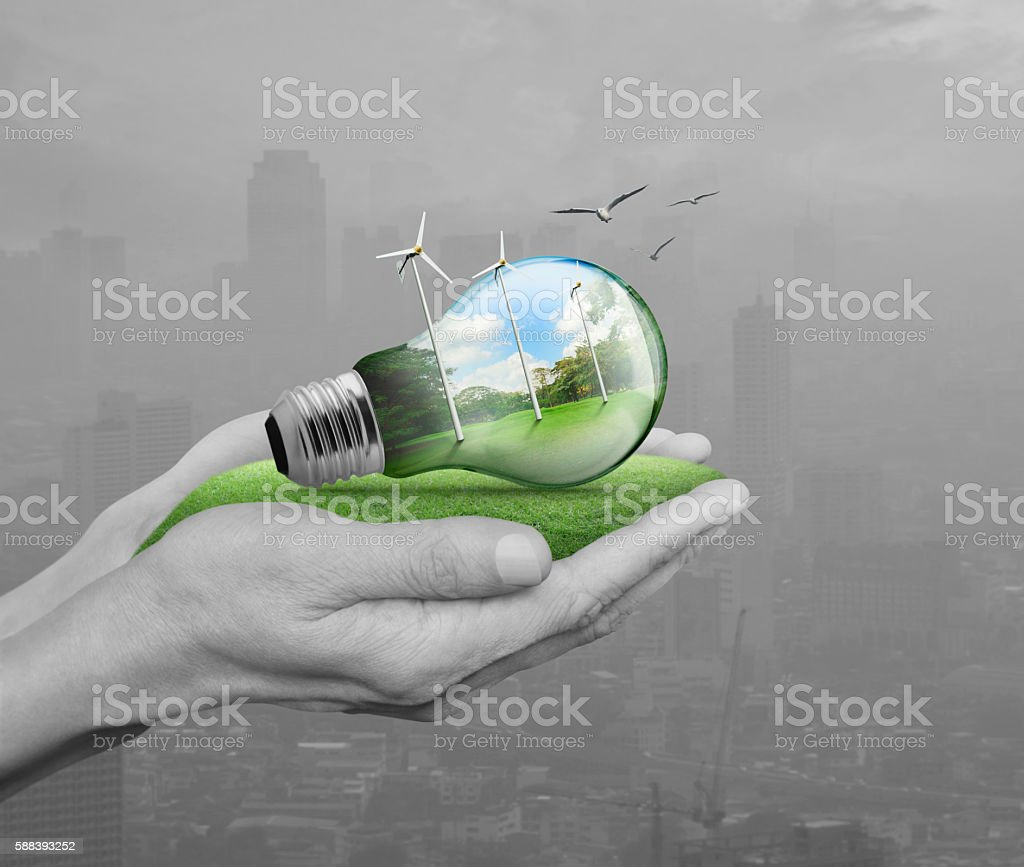Light bulb with wind turbines in hands over pollution city stock photo