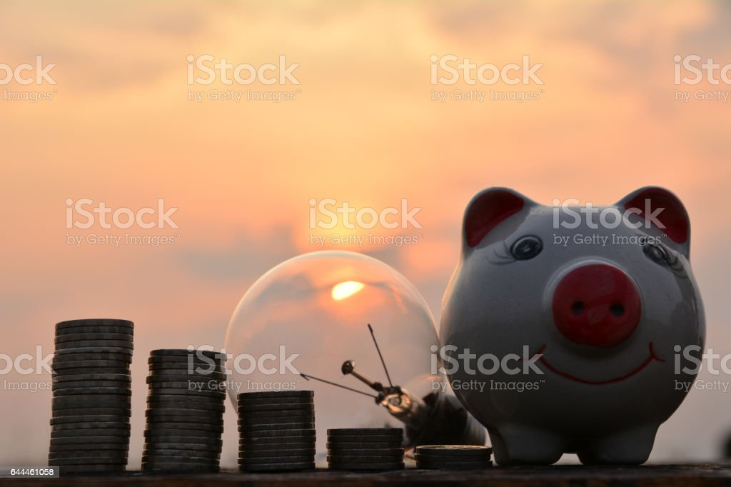 light bulbs and stack coins idea concept and silhouette style stock photo