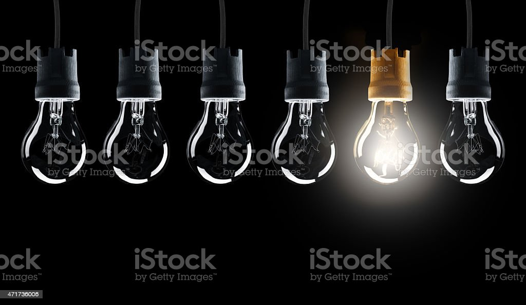 Light bulbs in row with single one shinning stock photo