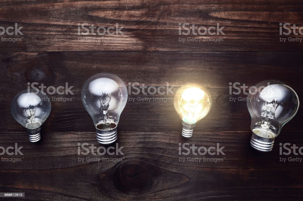 4 light bulbs on a wooden background, one light is on, concept ideas,...